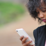 [Image Description: Black woman in a blazer looking at her phone outside.]