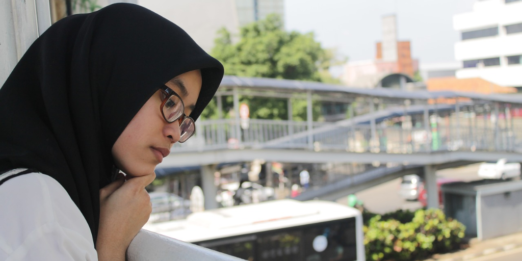 Young woman wearing glasses and hijab staring out the window at the street below her
