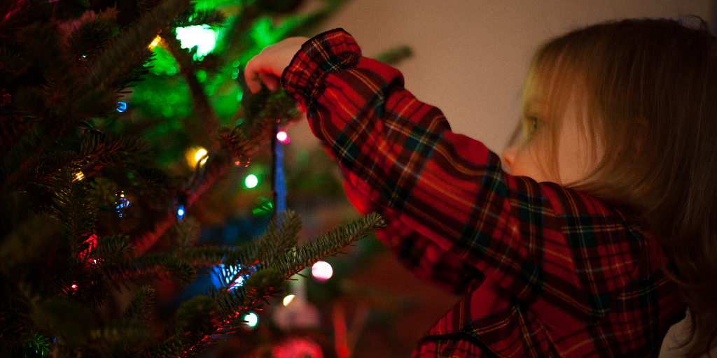 Young light skinned girl hanging an ornament on a Christmas tree