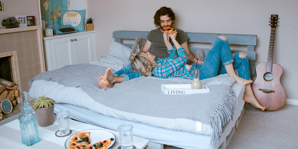 A light skinned woman and a light skinned man in the bed in their bedroom fully clothed. The woman is feeding the man a slice of pizza.
