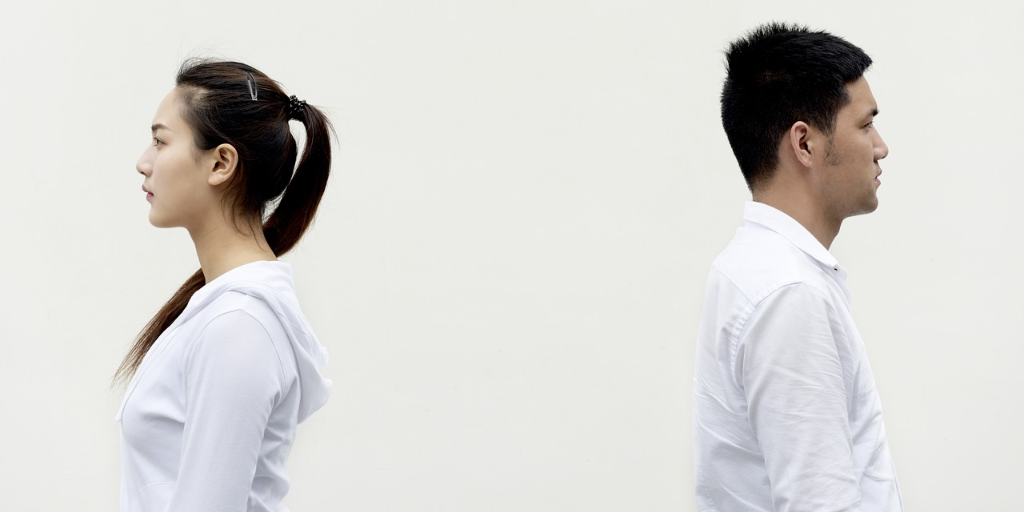 Asian man and woman both wearing white standing a good distance from each other back to back.