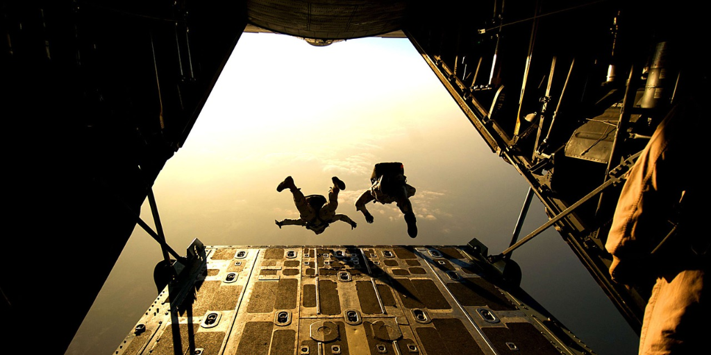 Two people jumping out of a plane to go skydiving