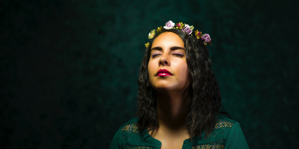 Image description: A woman standing in the dark with her face towards an overhead light. Her eyes are closed and she looks like she is at peace. She has long, dark hair and is wearing a flower crown.