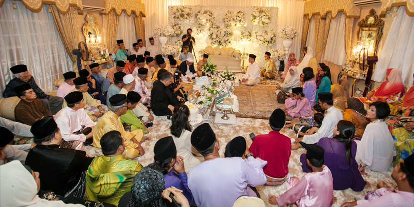 [Image description: Guests sit on the floor with their legs crossed around a wedding ceremony taking place. Everyone is wearing traditional clothes and the room is ornately decorated. From stories.my]