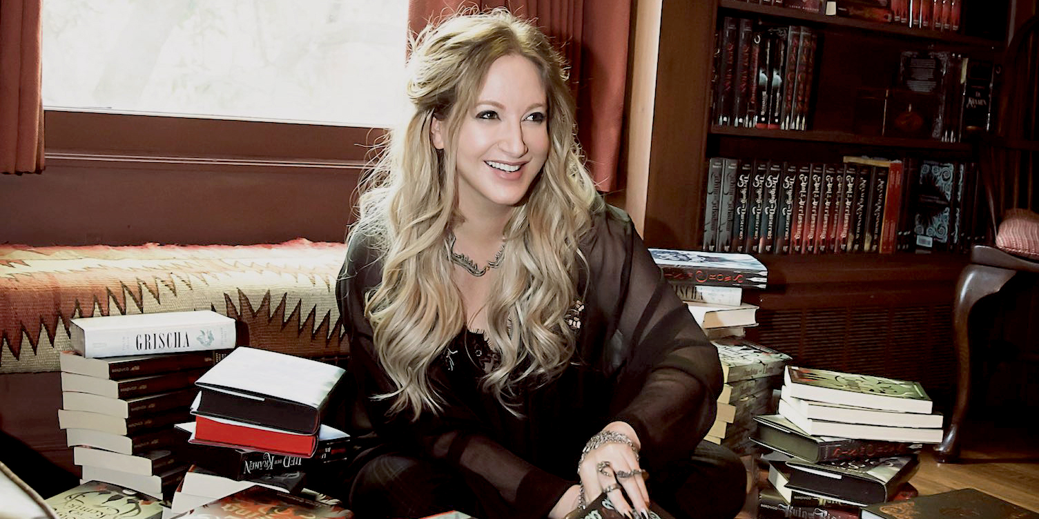 [Image description: The author Leigh Bardugo, a blonde woman, is pictured sitting on the floor, surrounded by different language editions of her own books.]
