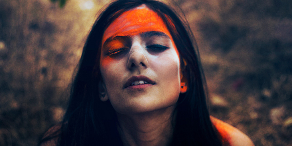 Dark skinned woman with orange and white paint across her face