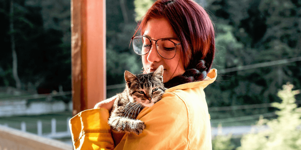 Woman with read hair and classes holding a calico cat