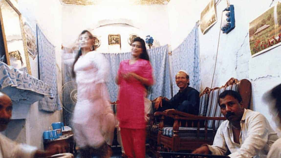 [Image description: Two sex workers dancing as musicians play the tabla.] via pbase.com