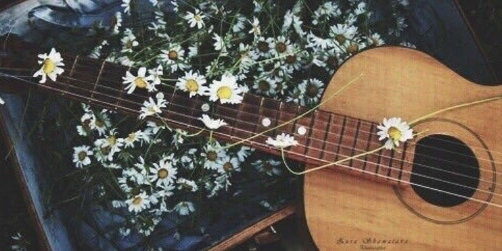 An acoustic guitar in the midst of flowers.