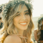 [Image description: A woman wearing a flower crown looks straight at the camera. She has blonde hair and is smiling widely. Behind her are other women also wearing flower crowns. Image source: unsplash.com]