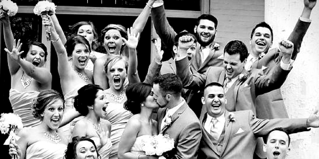 [Image description: a wedding party celebrating the marriage of a bride and groom. The bride and groom are kissing in the center of the group. Image source: tensixteenphoto.com]