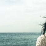 A photo of an off-center woman with black hair looking out towards the ocean.