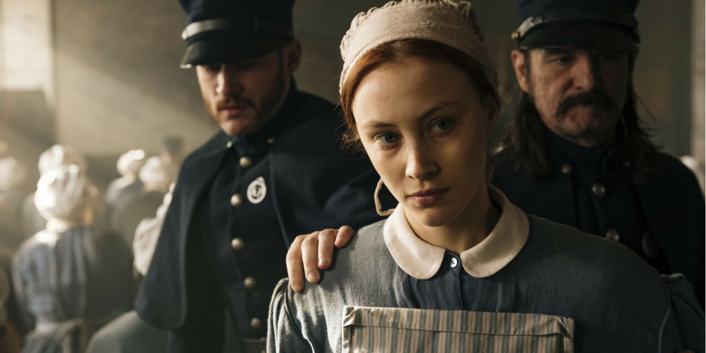 """A screencap from the show """"Alias Grace."""" A woman in traditional Quaker-style clothing is scowling as she is being held by two men in police officer uniforms. One of the men has his hand on the woman's shoulder."""
