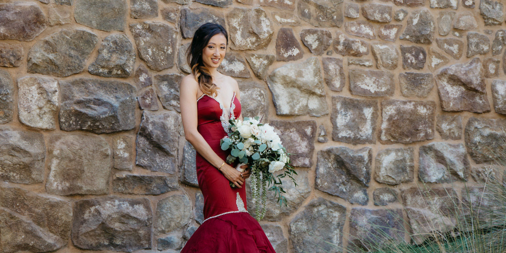 [Image description: A bride wearing a mermaid-style red wedding dress stands against a stone wall. She is carrying a big, beautiful bouquet of flowers and smiling widely.]