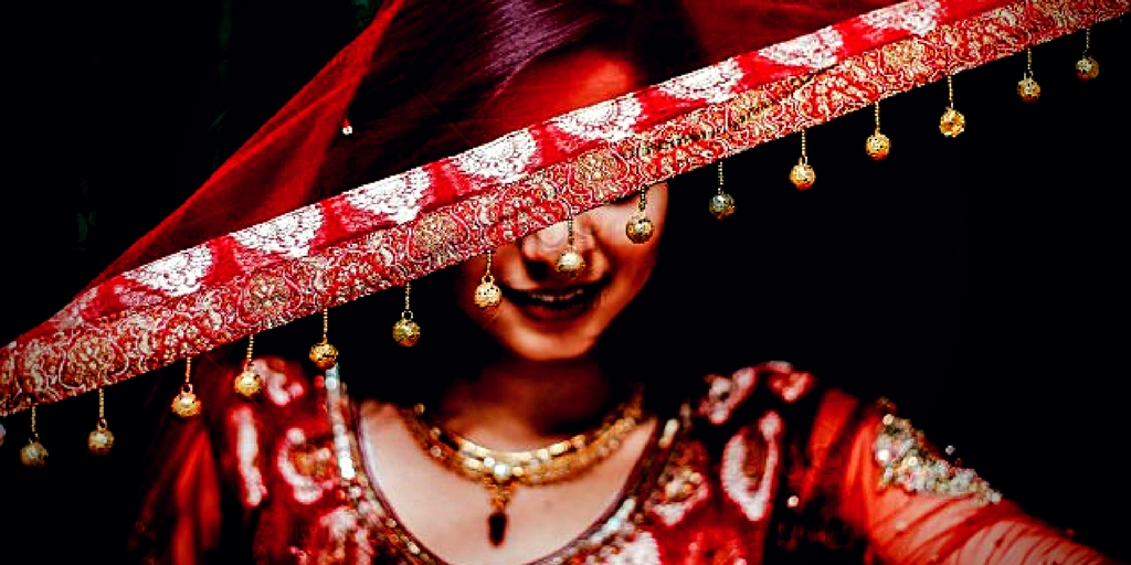 [image description: A Desi woman wearing a traditional red outfit is holding a piece of fabric across her eyes. She is smiling in a playful manner.]