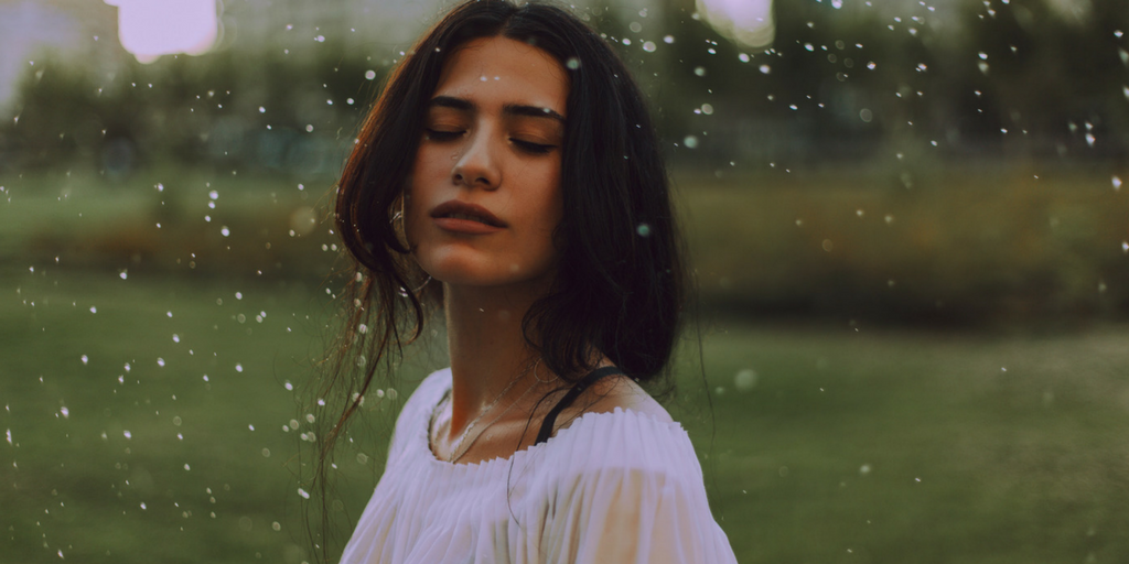 A woman stands with her eyes closed as rain falls.