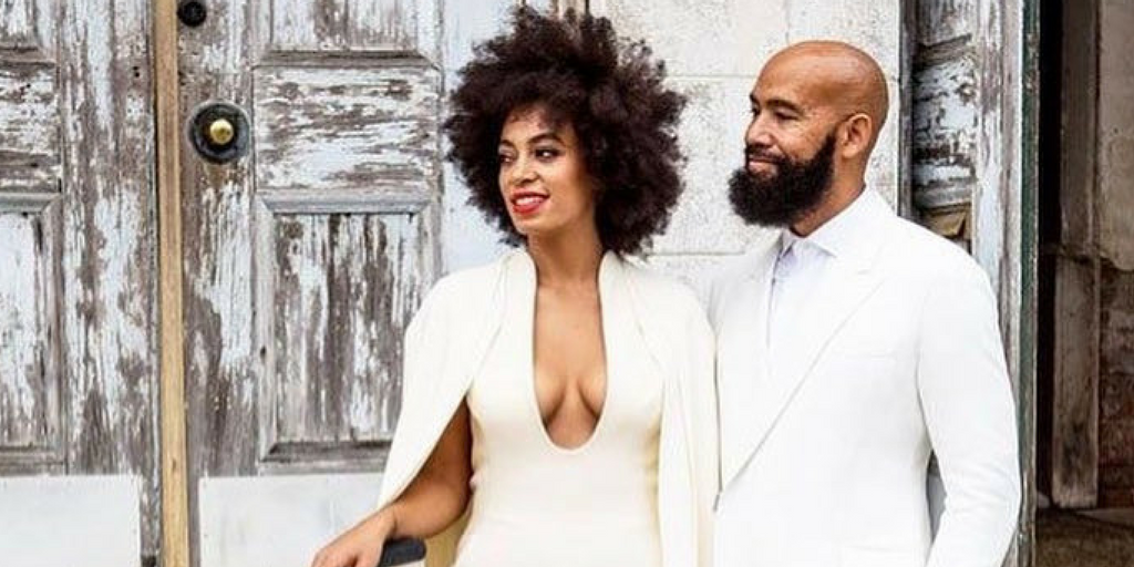 [Image description: Solange Knowles and her husband standing together on their wedding day and smiling. Image source: Instagram]