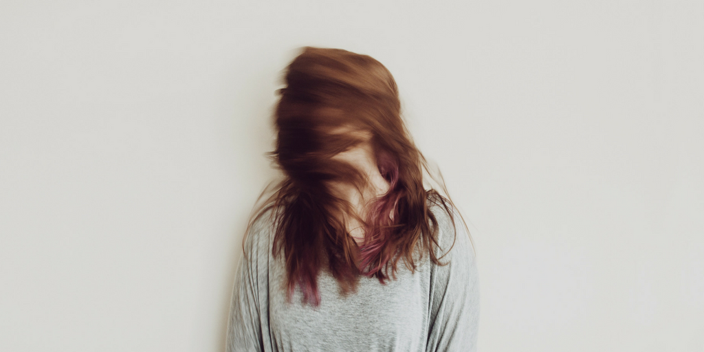 Red-headed woman with hair covering her face stands against a blank white wall.