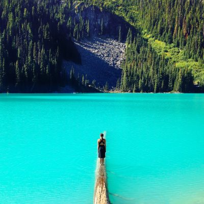 A woman stands on a log in a bright blue lake, looking out toward a mountainside filled with trees.