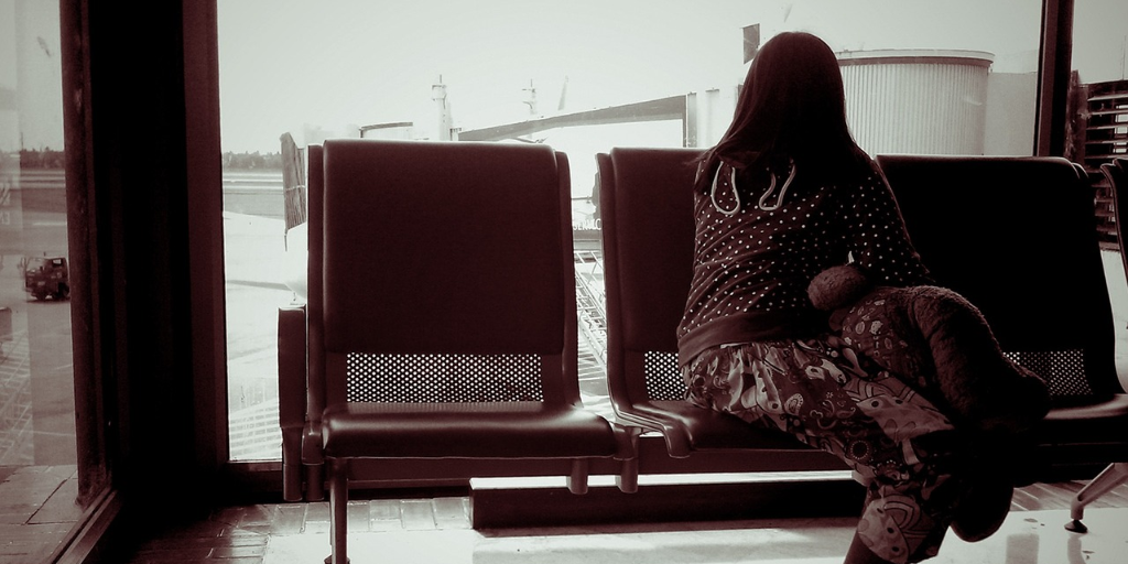 Woman sitting in a chair at the airport looking out the window