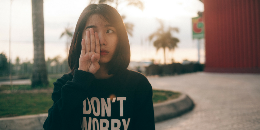 Young girl stands in the sun with one hand covering her eye, wearing a sweatshirt that says DON'T WORRY.