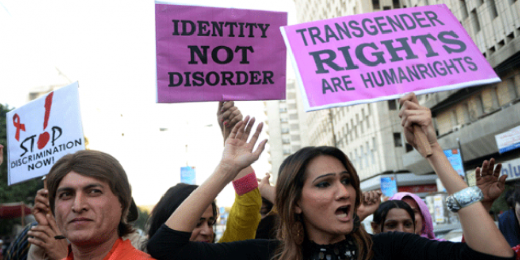 Brown transgender women protesting for their rights with signs in hand.