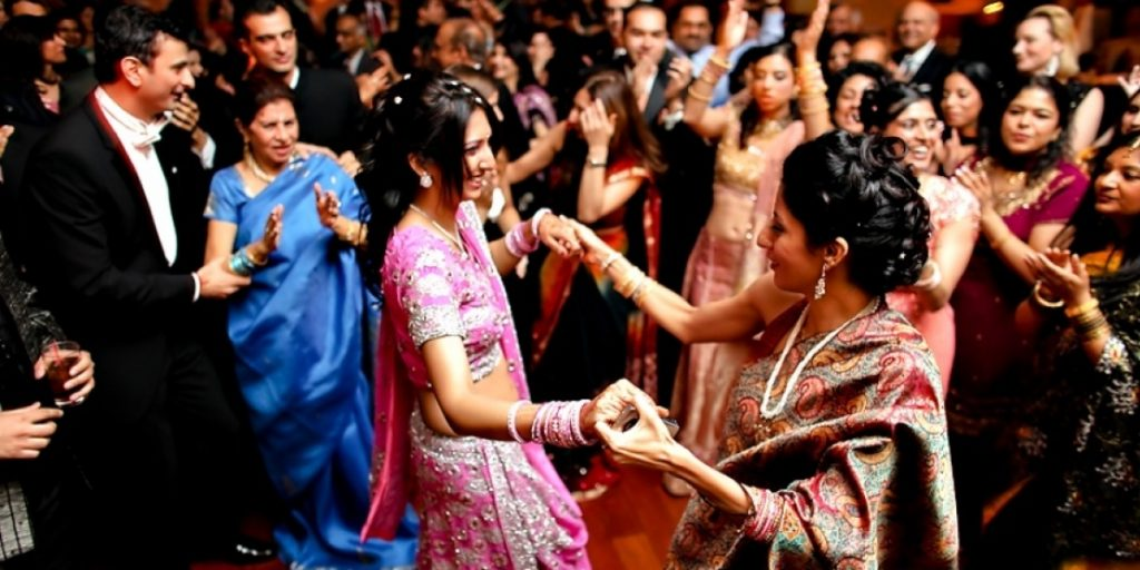 Attribution: [Image description: guests are celebrating a South Asian wedding. In the front are two women wearing traditional dress, holding each other's hands and dancing.] Via weddingstreet.in