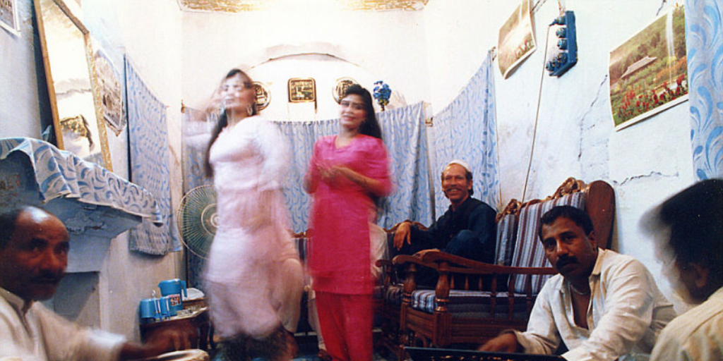 Two prostitutes dancing as musicians play the tabla