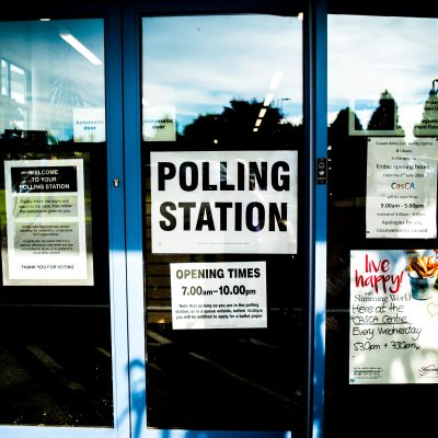 "A picture of a glass door with a ""polling station"" sign taped to it."
