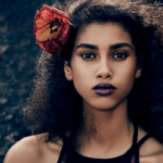 A girl with curly back hair with a red flower tucked in her ear casting a smoldering and fierce look.