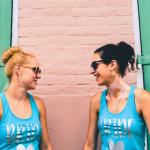 Two women wearing matching BRIDE shirts smile at each other against a green and pink wall.