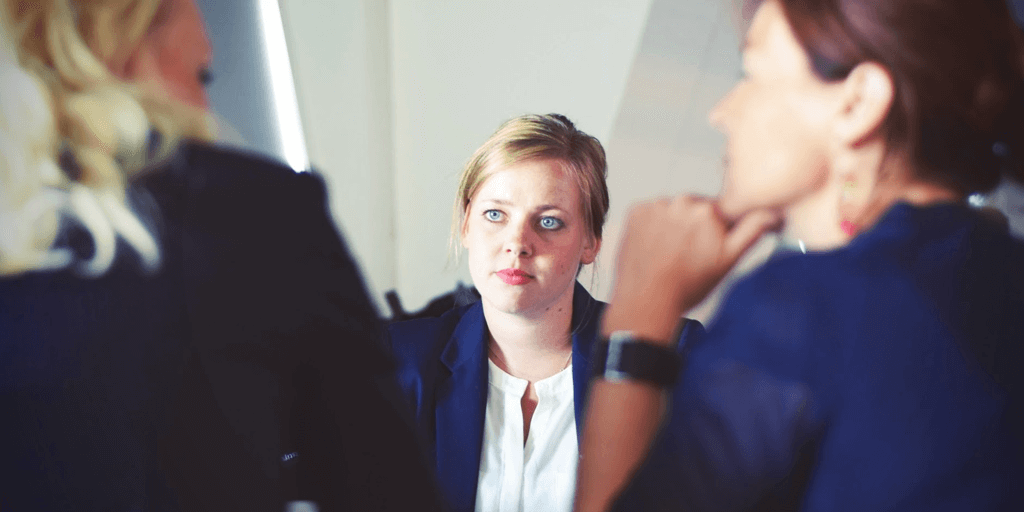 Blonde lady in work attire looking with a straight face, in front of 2 other women who seem to be engaged in conversation, both ladies are also in work attire.