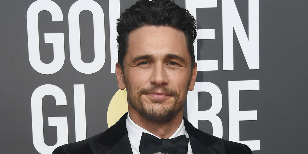 James Franco wears a tuxedo in front of a sign that says Golden Globe.