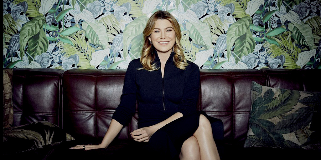 [Image description: woman sitting on dark sofa, grinning; photograph of Ellen Pompeo]