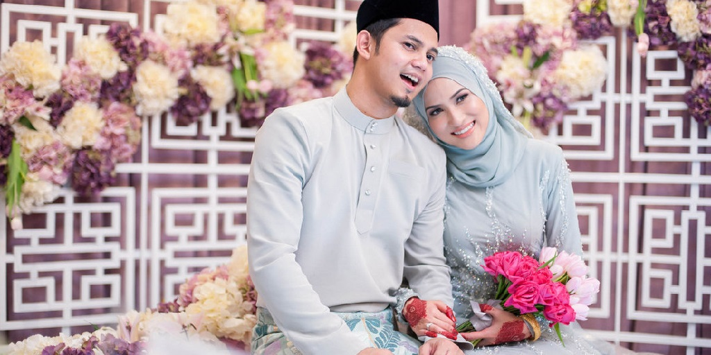 Attribution: [Image description: A Malaysian couple looking happy on their wedding day. Both are dressed in light-blue traditional dress. The bride is resting her head on the groom's shoulder and holding a bouquet of pink and white flowers.] Via Pinterest