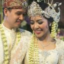 Attribution: [Image description: A Sundanese couple smiling at each other. They are dressed ornately for their wedding.] Via Pinterest