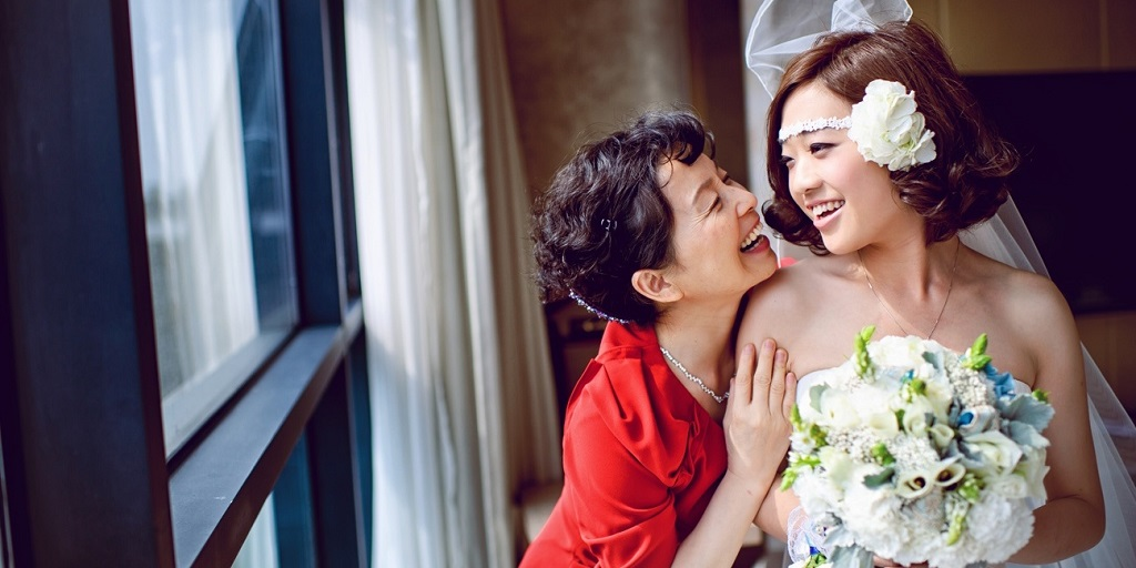 [Image description: A bride and her mother are smiling at each other. The bride is holding a bouquet of flowers. Image Source: I-do.com]