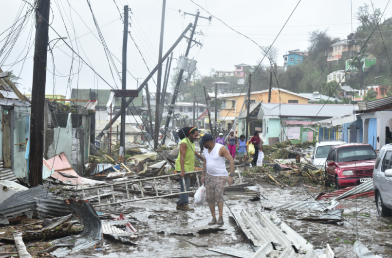 Photo of devastated homes and people walking amidst the rubble post Hurricane Maria in Puerto Rico.