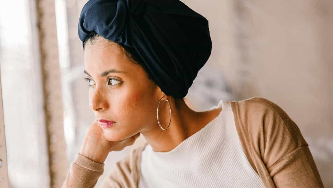 [Image description: Woman wearing a dark turban looks out the window.] Photo by mentatdgt from Pexels