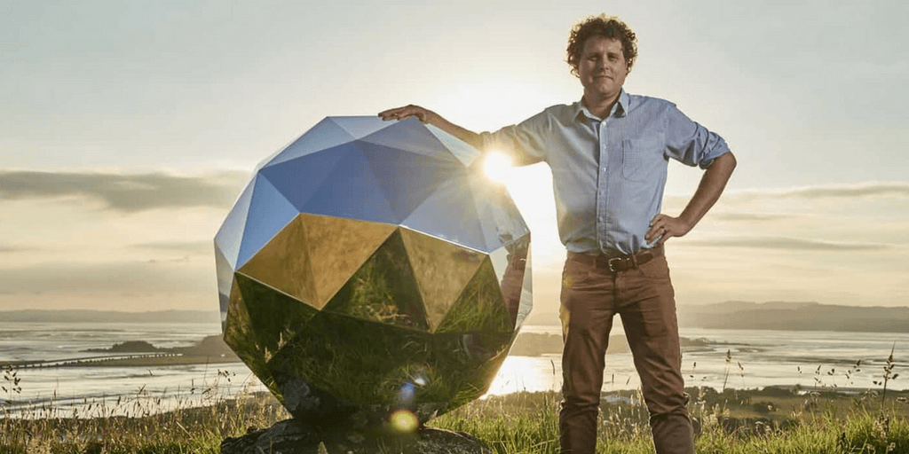 Rocket Lab's Humanity Star founder stood next to the star which is a silver object that comes up to his shoulders.