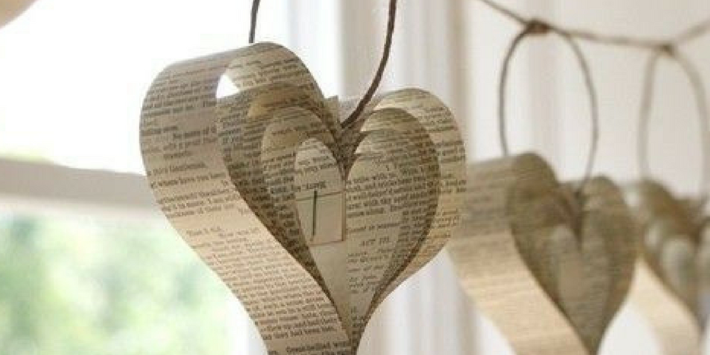 [Image description: pages cut out from a book and stuck together to create the shape of a heart hung from a rope. Image source: Pinterest]