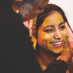 [Image description: Woman in bridal wear has paste put on her face in a cultural tradition.] via Unsplash