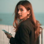 [Image Description: A woman with brown hair is holding a phone and looking back into the camera. She has a serene expression on her face.] Via Pexel