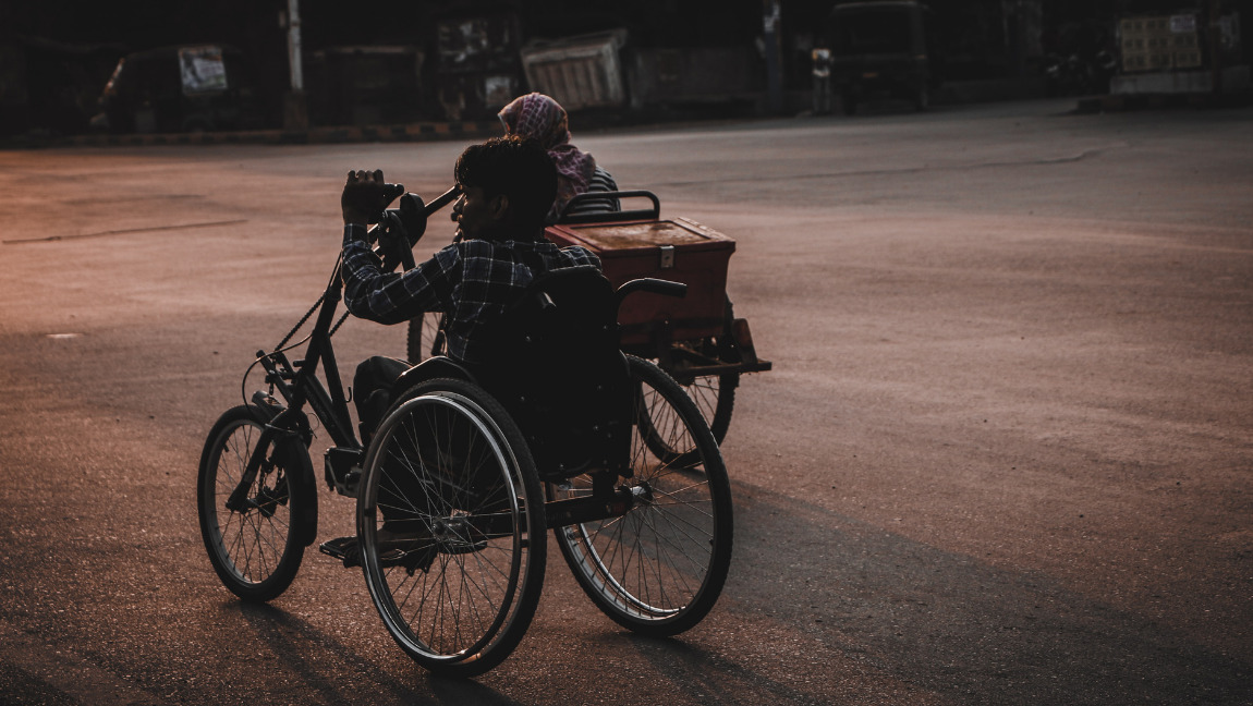 Image Description: A young man is sitting on a wheel chair. He is next to an older woman who is also on a wheelchair. They appear to be on the road side. [Via Unsplash]