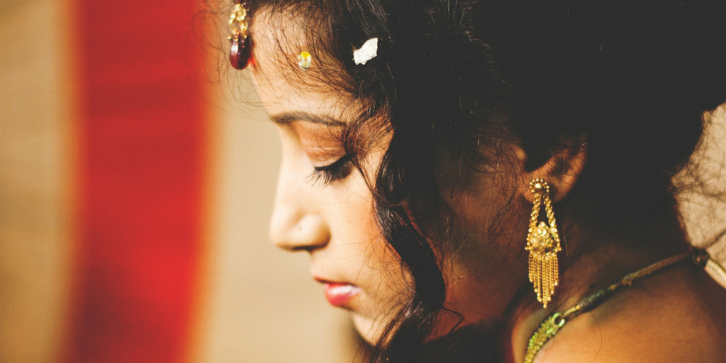 [Image description: A South Asian bride with a lowered gaze.] Via Pexels