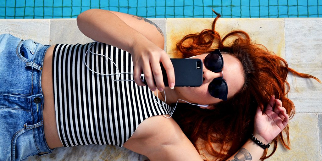A red-haired person is lying near a pool. They are checking their phone.