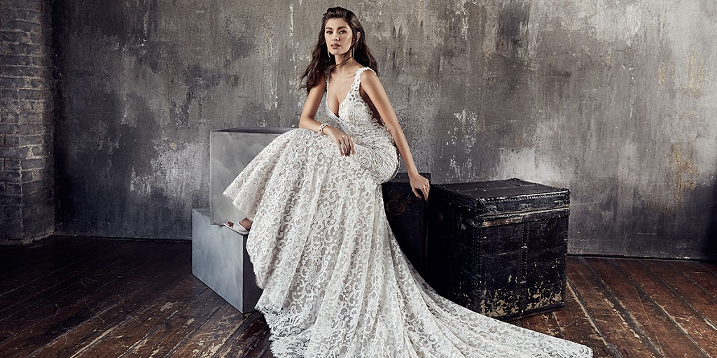 [Image description: A bride wearing a long, white lace wedding dress is sitting on a block. The dress is draped beautifully on the floor. Image source: eddyk.com]