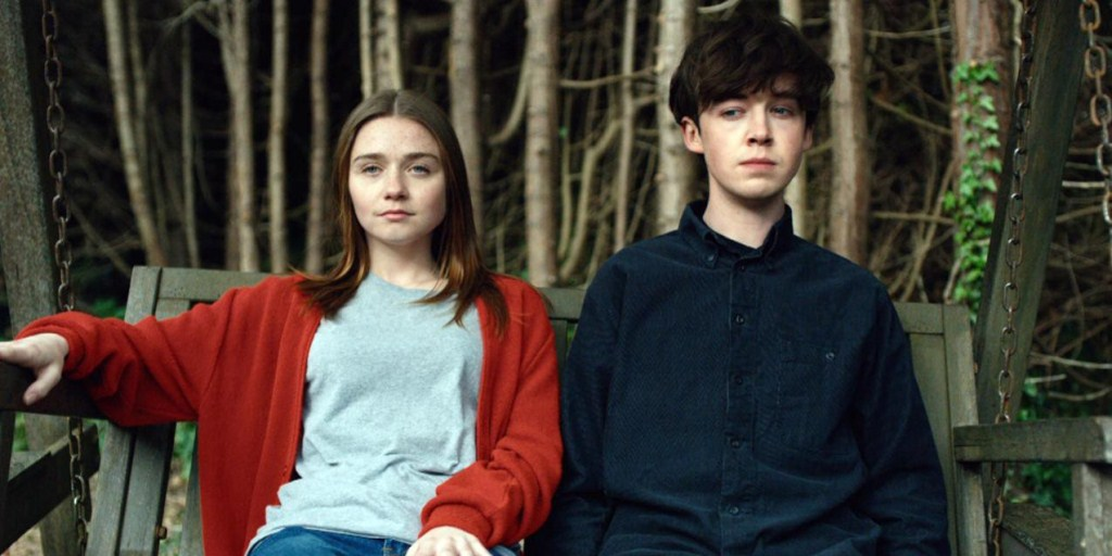 Alyssa and James, the two main characters from the Netflix series 'End of the F***ing World', sit next to one another. They're near a woody area, which can be seen in the background.