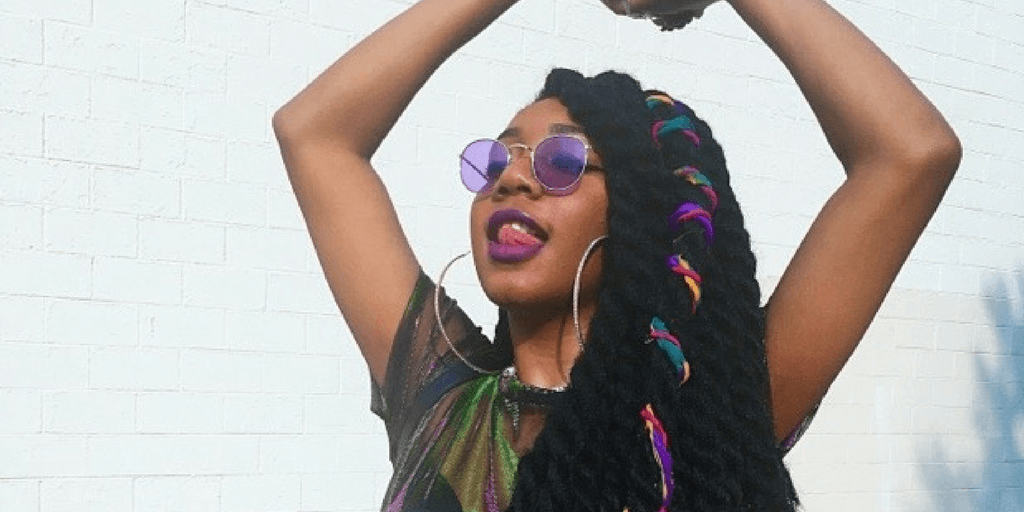 black girl with colorful twists and purple sunglasses poses, hands up in joy @kaleidoscopety