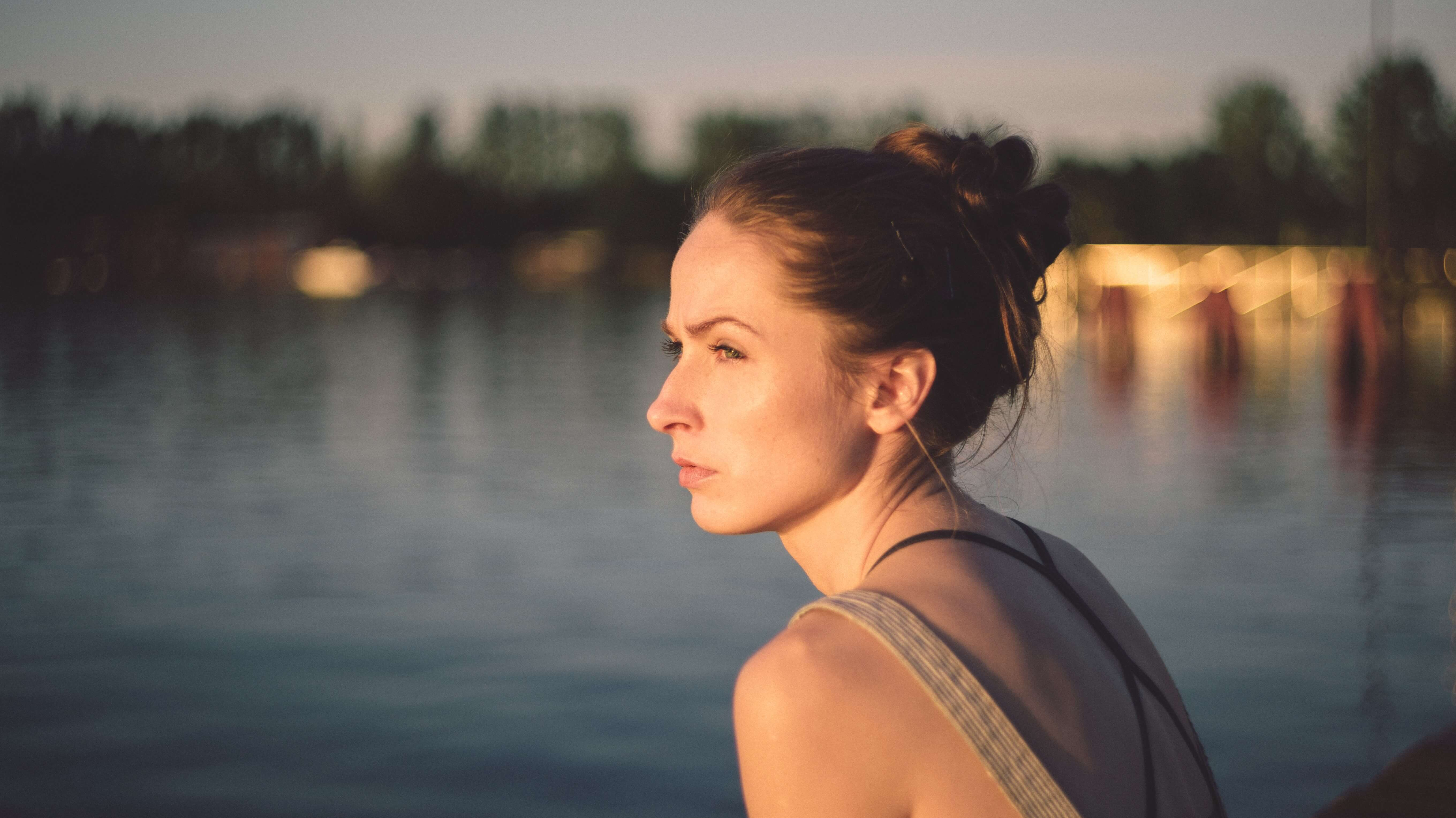 Image description: Young woman looking sadly across a lake.
